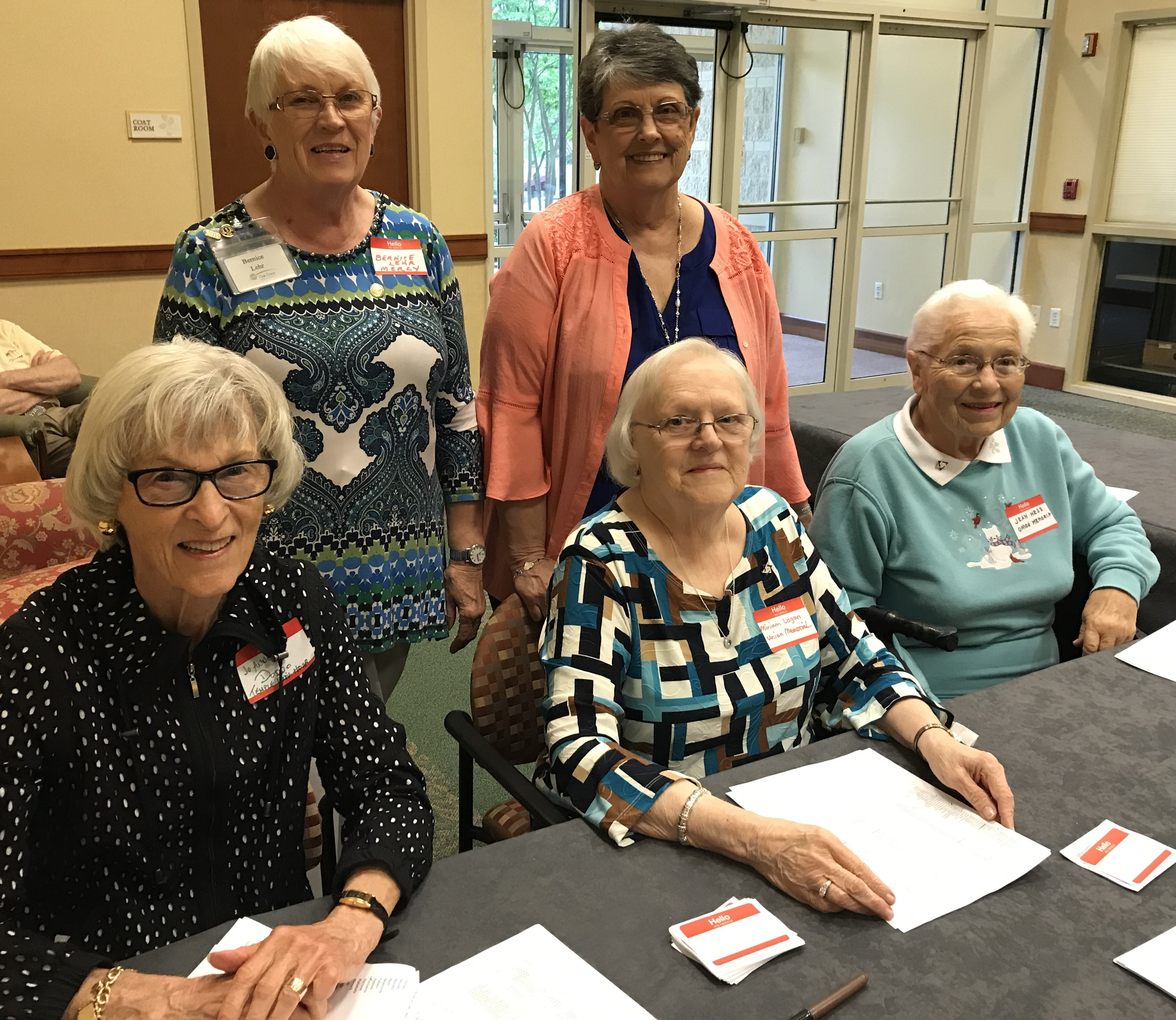 Four residents of Oak Crest are at the welcome table for the 2019 Annual Nurses' Week Luncheon.